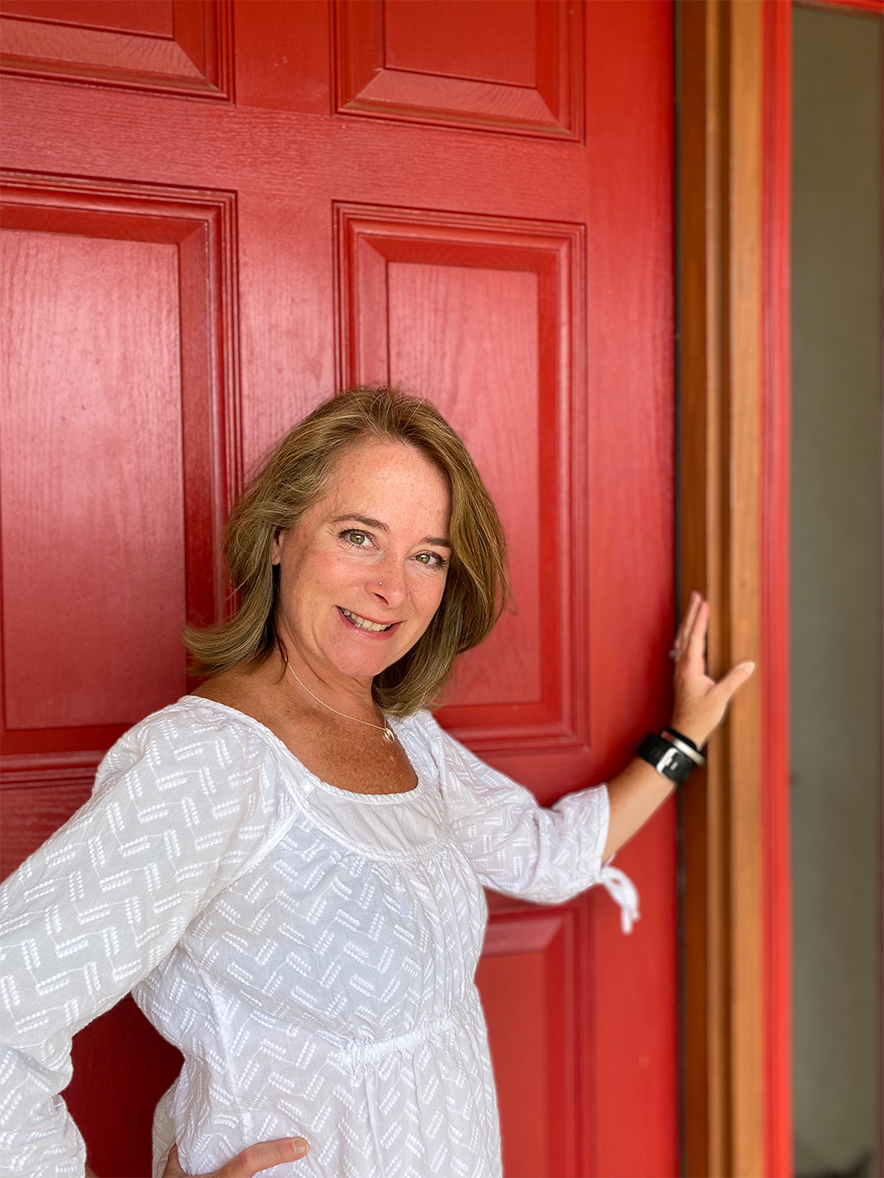 Ashley Lawless smiles, standing in front of a red door.